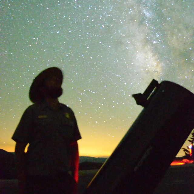 Ranger next to a telescope at night