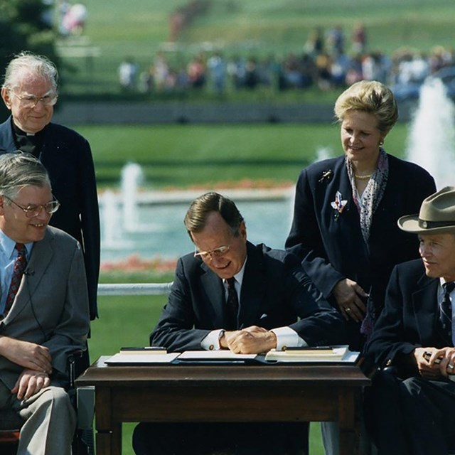 President GHW Bush signs the ADA 1990. National Museum of American History photo