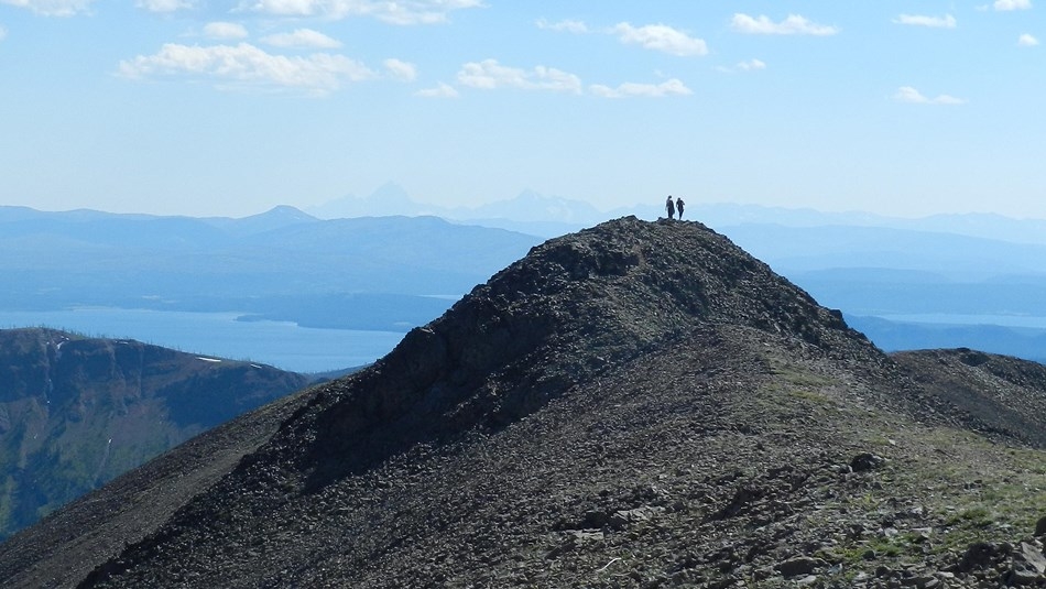 Hikers standing on the rocky top of Avalanche Peak with Yellowstone Lake in the background.