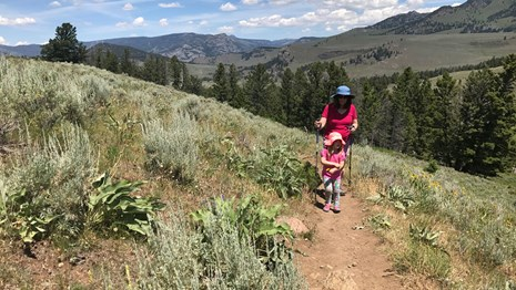 Daughter and mother hike up a trail along the Yellowstone River.