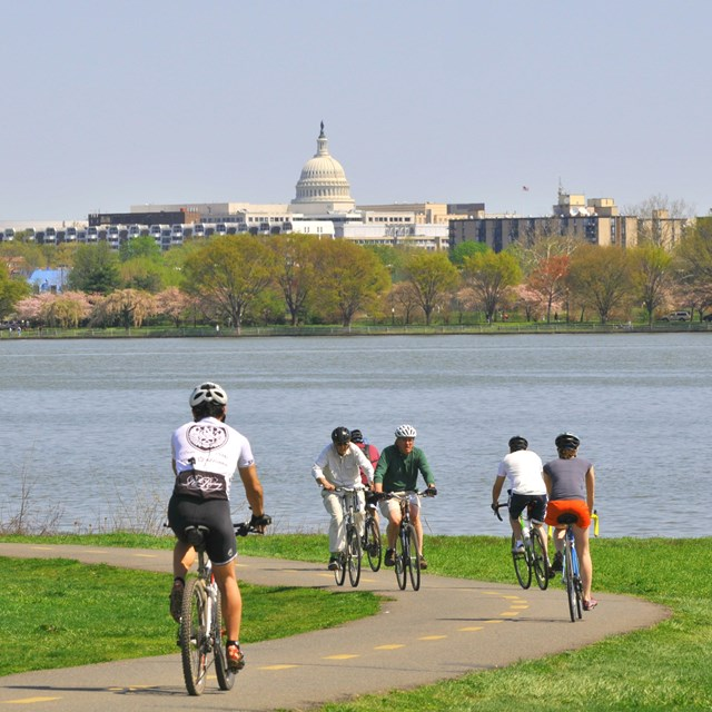 Cyclists on the Mount Vernon Trail across from Capital Hill.