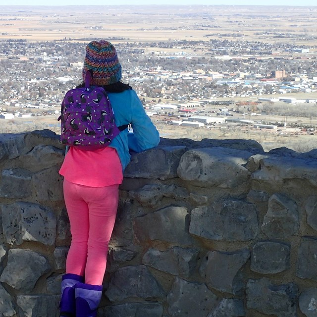 A young hiker stands at the North Overlook, looking down on the town of Scottsbluff.
