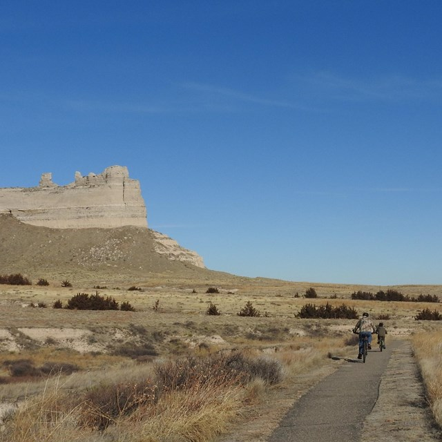 A pair of bicyclists rides on a trail with an impressive rock formation in the background.