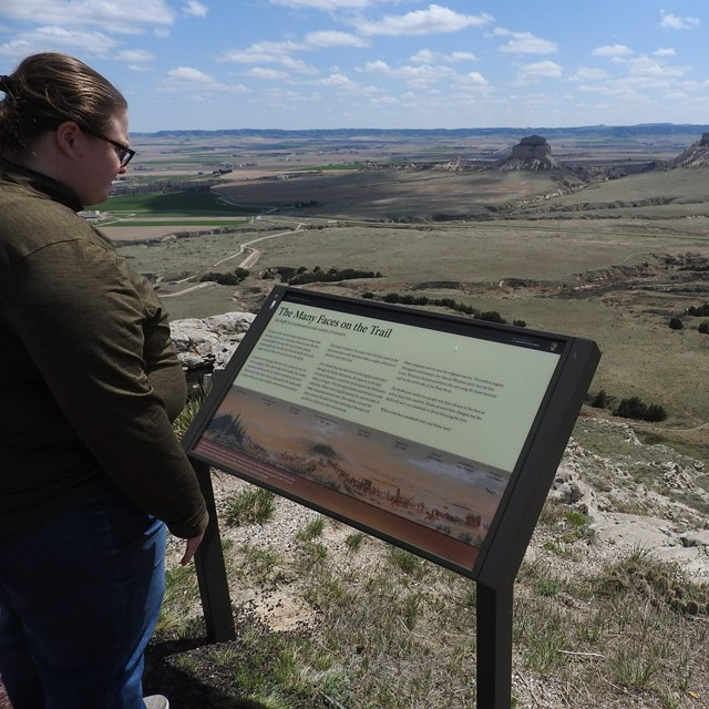 A woman reads an interpretive panel at an overlook of a valley and surrounding bluffs.