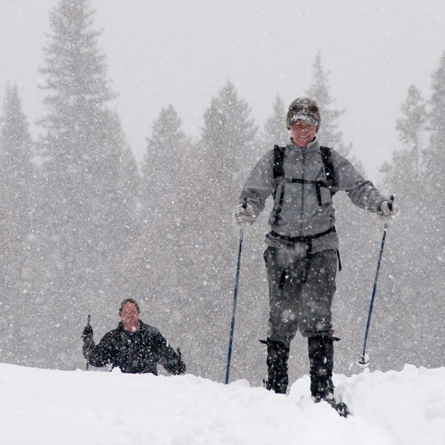 Two cross country skiers appear over a small hill during a snow storm.