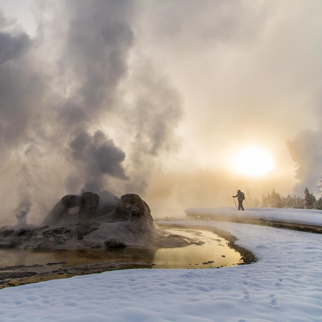 A lone visitor enjoys castle geyser from a snowy boardwalk just before sunset.