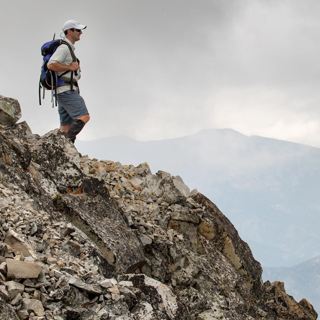 Male day-hiker standing atop a rocky mountain.