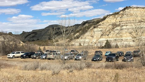 Twenty vehicles parked in a gravel lot at a trail head surrounded by trees and layered buttes.
