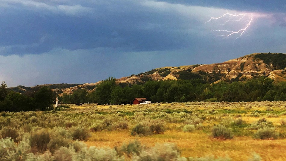 Lightning crackles from behind a dark blue cloud atop an open prairie with a butte behind.