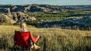 A person sits in a camp chair on the prairie overlooking the badlands