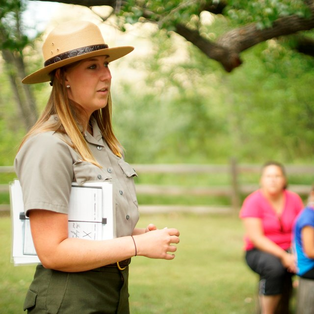 A ranger stands in front of a group of seated park visitors