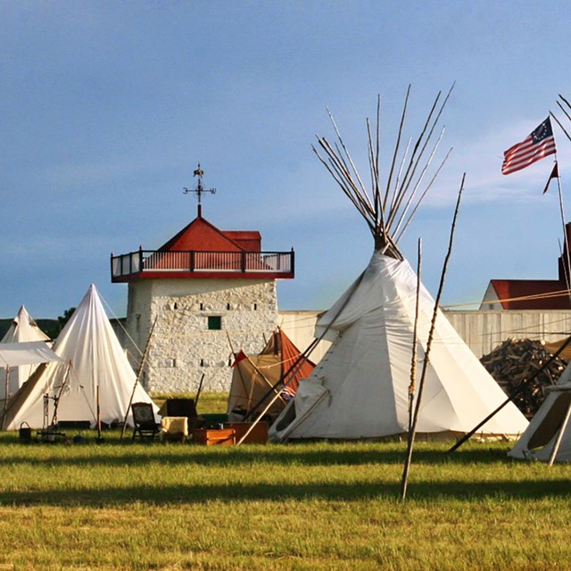 Green grass, blue cloudy sky, white tipis in front of a white fort wall and bastion with a red roof