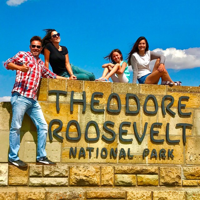 A smiling family poses atop the park's stone entrance sign.