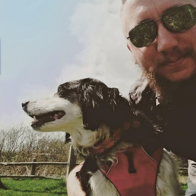 A dog wearing a harness and leash and his human wearing sunglasses take a selfie together.