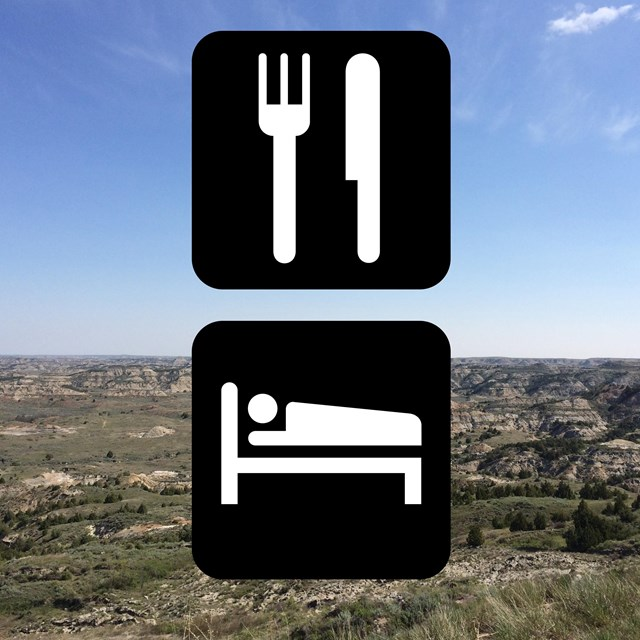 international symbols for lodging and dining in front of a badlands scenic backdrop