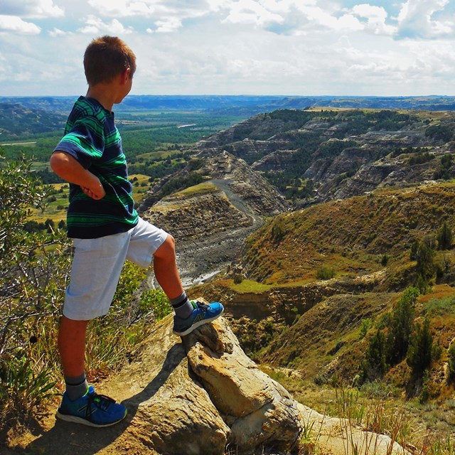 A child looks out into the sunny badlands with hands on hip and foot resting atop a rock.