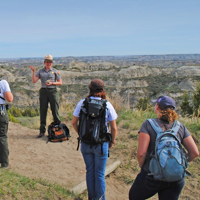 A ranger and group of park visitors standing along a trail on a grassy ridge.