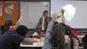 Ranger pointing at children with hands raised in a classroom