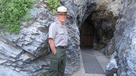 Ranger standing by the entrance to Hansen Cave