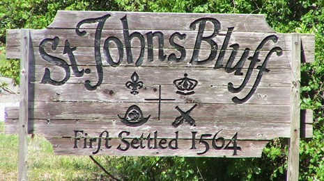 a wooden sign for St. Johns Bluff