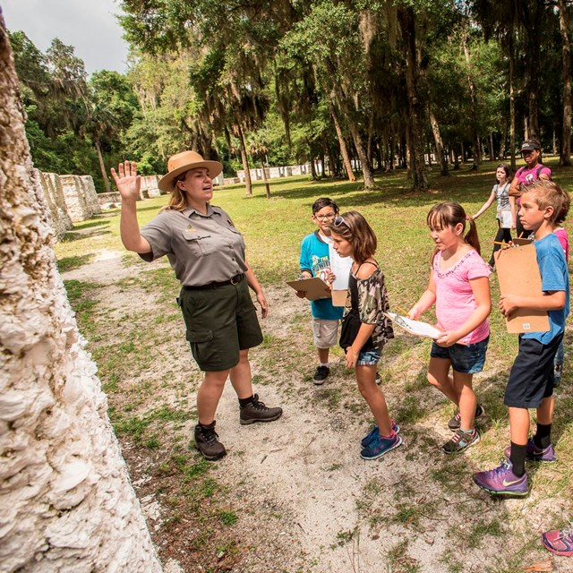 a ranger points to a slave cabin while school children follow