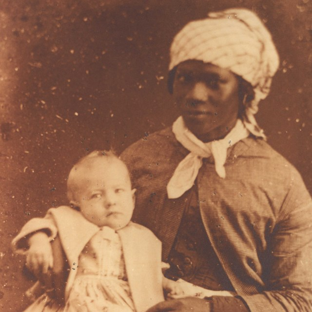 enslaved woman holding her owners child