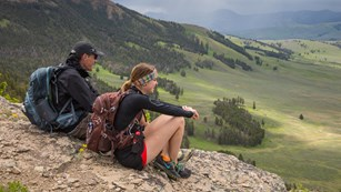 Two people sit on a rock looking at rolling green hills.