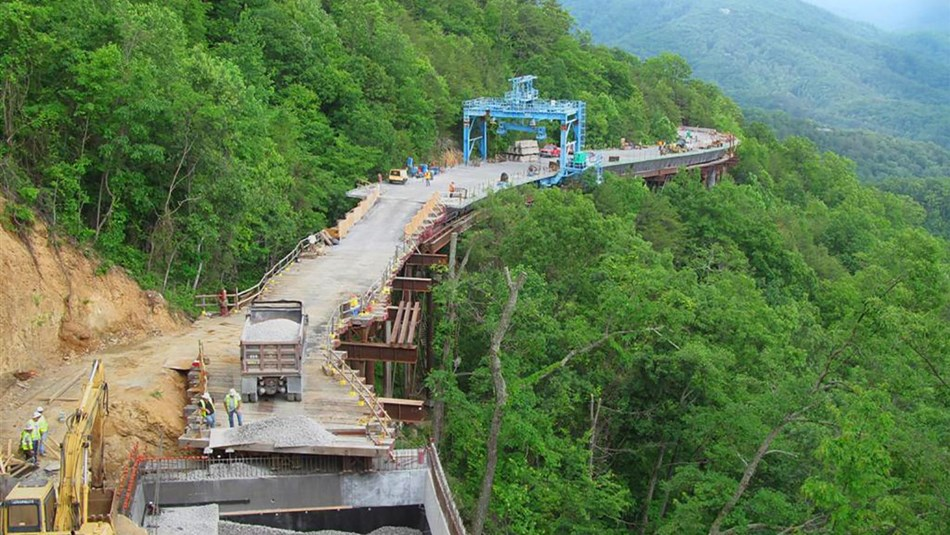 a big construction  project on the road on the side of a wooded mountain