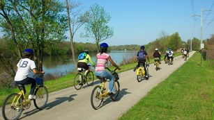a group of young people biking on a bike path next to a body of water