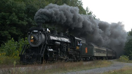 an old black locomotive, smoke coming out of the top