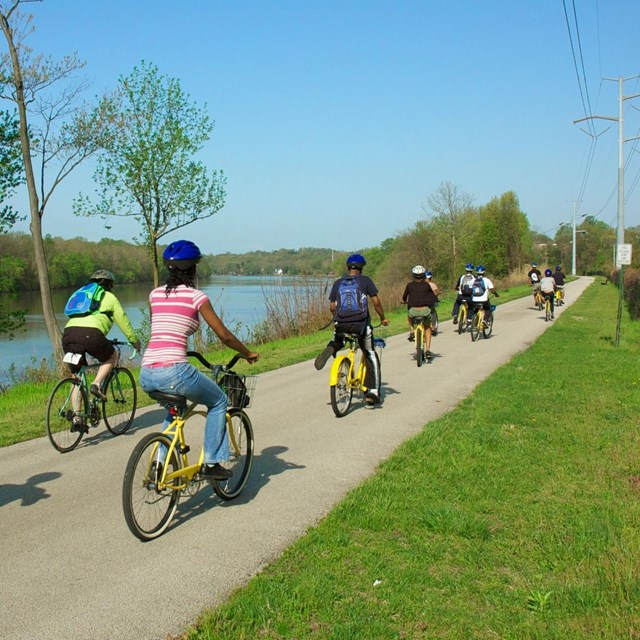 Group riding bikes on paved path next to body of water