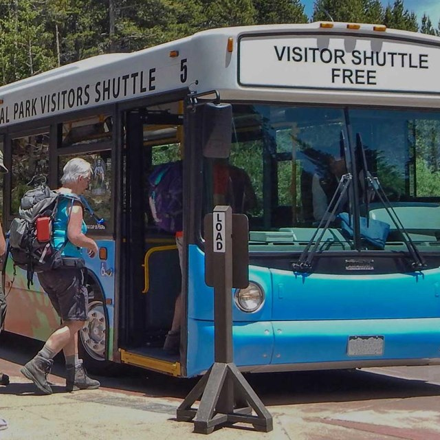 tourists get on a bus in Rocky Mountain National Park