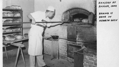 man taking bread out of the oven