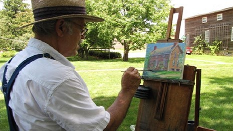 man painting outside of the amana arts guild