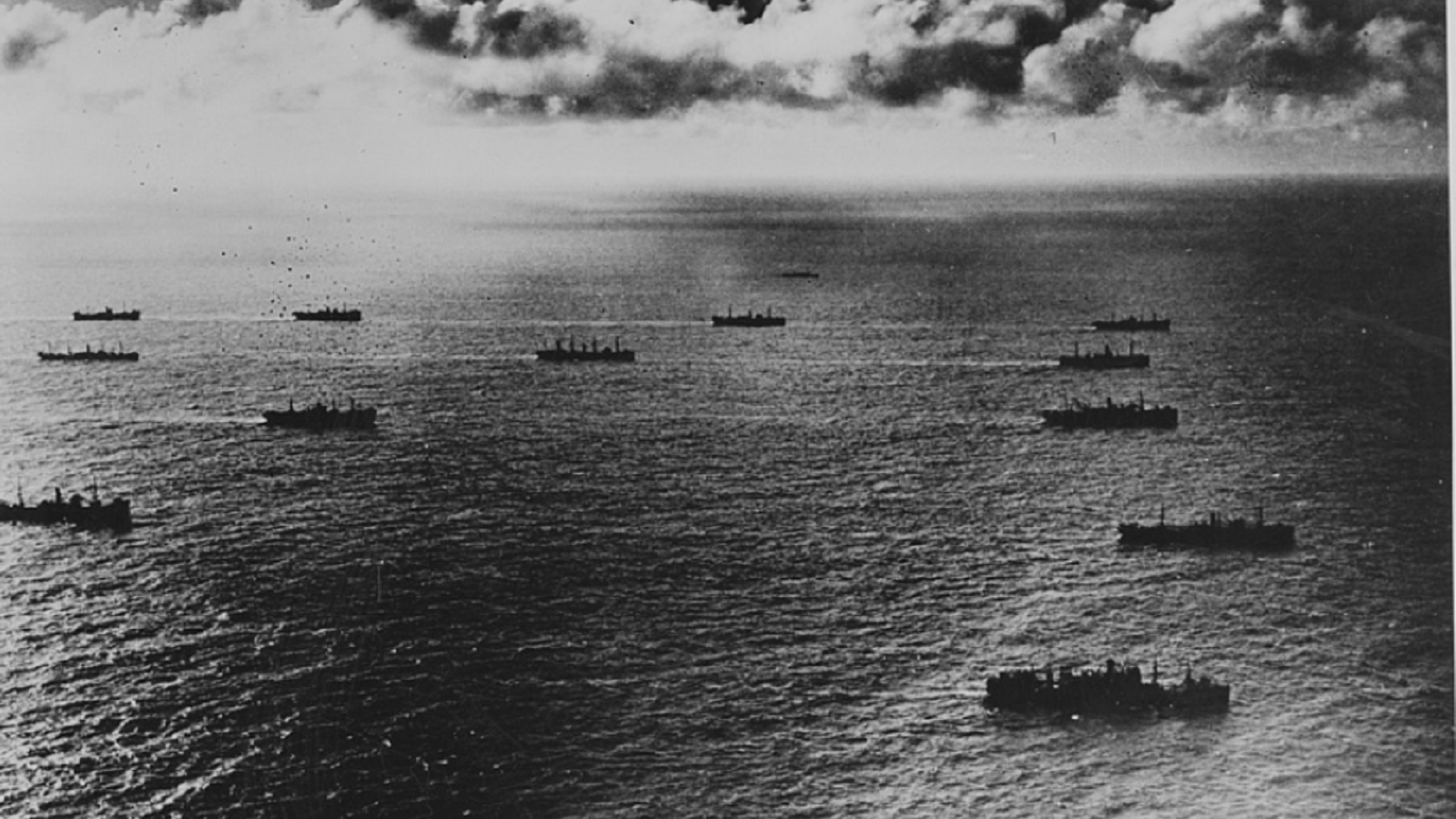 1940s black and white photo depicting several ships on the ocean.