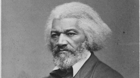 An older Frederick Douglass with white hair, sitting.