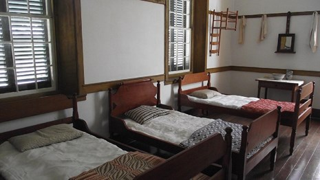 shaker bed room with three beds, wooden bed frames, and simple quilts