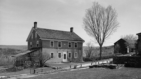 black and white photo of a brick building in a rural setting