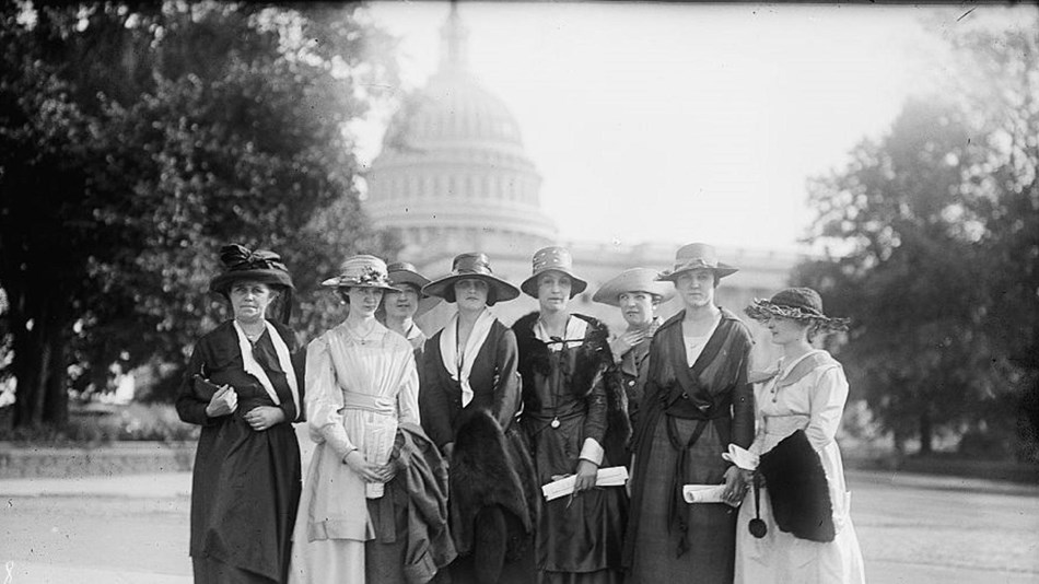 Group of women in early 20th century closing standing in front of Capitol Building.