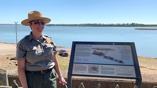 A uniformed park ranger stands next to a wayside exhibit along a river.
