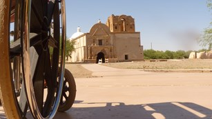 wheelchair and paved trail in foreground with church in background