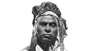 historic photo of native man with head covering, vest, and necktie