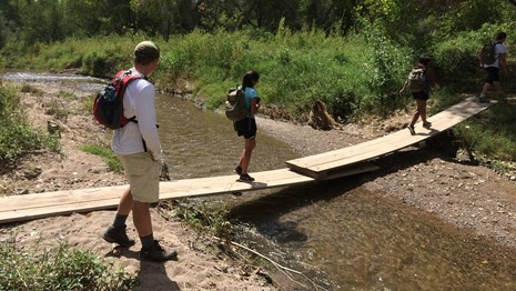 young hikers on plank bridge, spaced apart