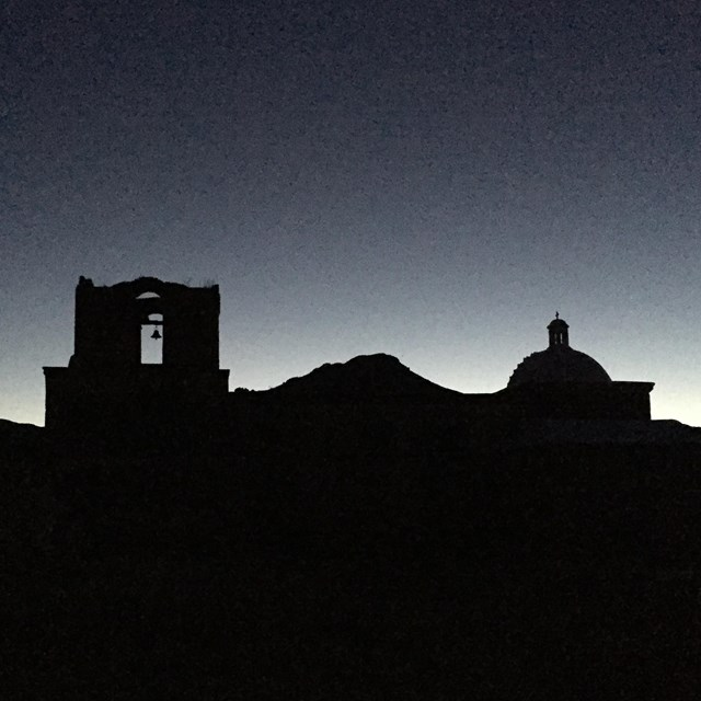 silouette of bell tower and dome in front of mountains against night sky