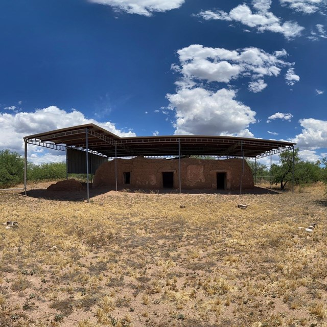 adobe structure with metal shed roof above
