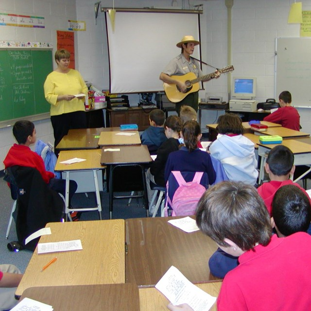 ranger playing guitar in front of classroom of students