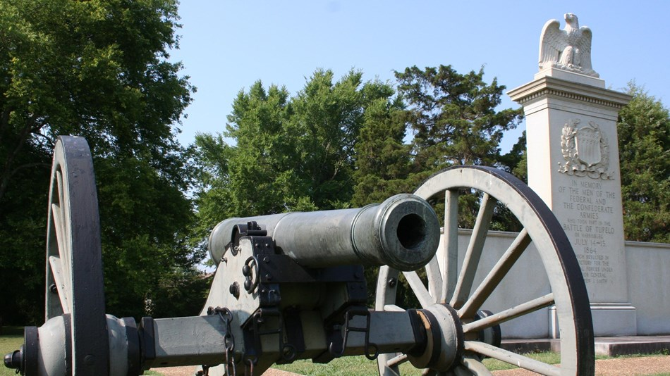 A cannon in front of the stone monument to the battle.