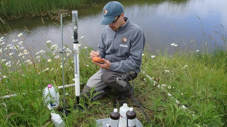 A network employee calibrating water quality instruments