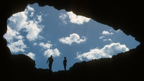 Looking out at the sky and two visitors from within the darkness of a cave