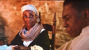 Screenshot of an African-American woman in period clothing, African-American man in the foreground.